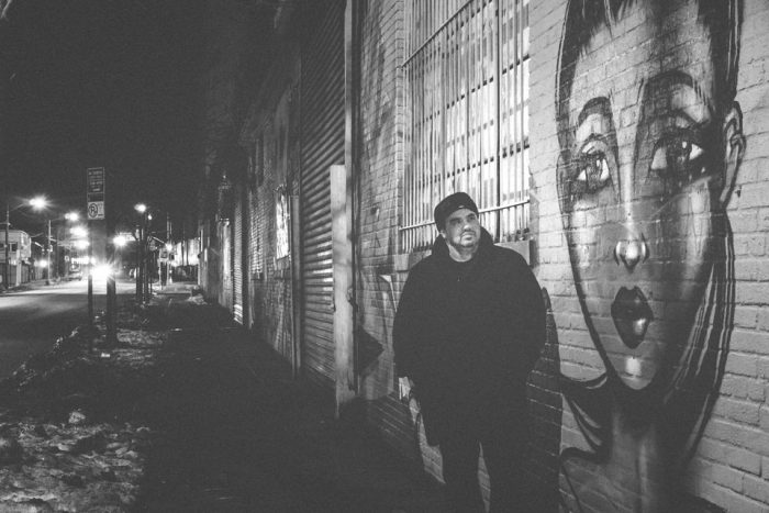 Eduardo Vega Colon standing in front of a street mural at the Bushwick Collective in Brooklyn at night