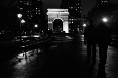 People in silhouette in Black and White photo at night of arch inside Washington Square Park in Greenwich Village. Street Photography with Fujifilm.