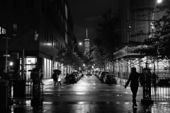 People in silhouette facing south from Washington Square Park staring at One World Trade Center building in the distance. Black and White photo in Greenwich Village. Street Photography with Fujifilm.