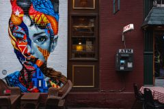Audrey Hepburn eye-catching street art mural by Tristan Eaton. Rainy day on the Mulberry Street in Little Italy in Lower Manhattan Street Photography with Fujifilm.