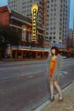 Young woman standing along Congress Avenue in Austin Texas for Glamour Photography photo shoot. Paramount Theatre marquee in the backdrop.