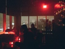 View of Manhattan at night from inside the Le Bain Standard Hotel with red light and people in silhouette.