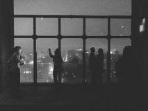 Rooftop view of Lower Manhattan with silhouette of people against the night sky at the Le Bain Standard Hotel