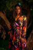 Indian American models in royal purple dress with flowery pattern standing in front of a tree, in the woods in Austin, Texas