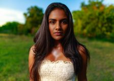 Indian American models in white tube top standing in front of a tree, in the woods in Austin, Texas