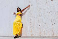 Black Girl Magic with Model in bright yellow dress posing at the Lyndon Baines Johnson Library and Museum, also known as the LBJ Presidential Library, on a hot summer's day.