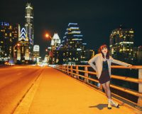 Model dressed like Harley Quinn for moody editorial fashion portrait photography on Congress Avenue Ann Richards Bridge with Texas State Capitol in the background