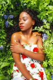 Black Girl Magic with African American woman resting on a bed of bluebonnet flowers.