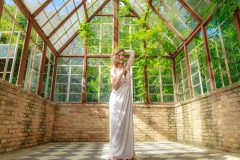 Seductive boudoir pictures of woman wearing white lingerie posing in the greenhouse at the sekrit theater in austin
