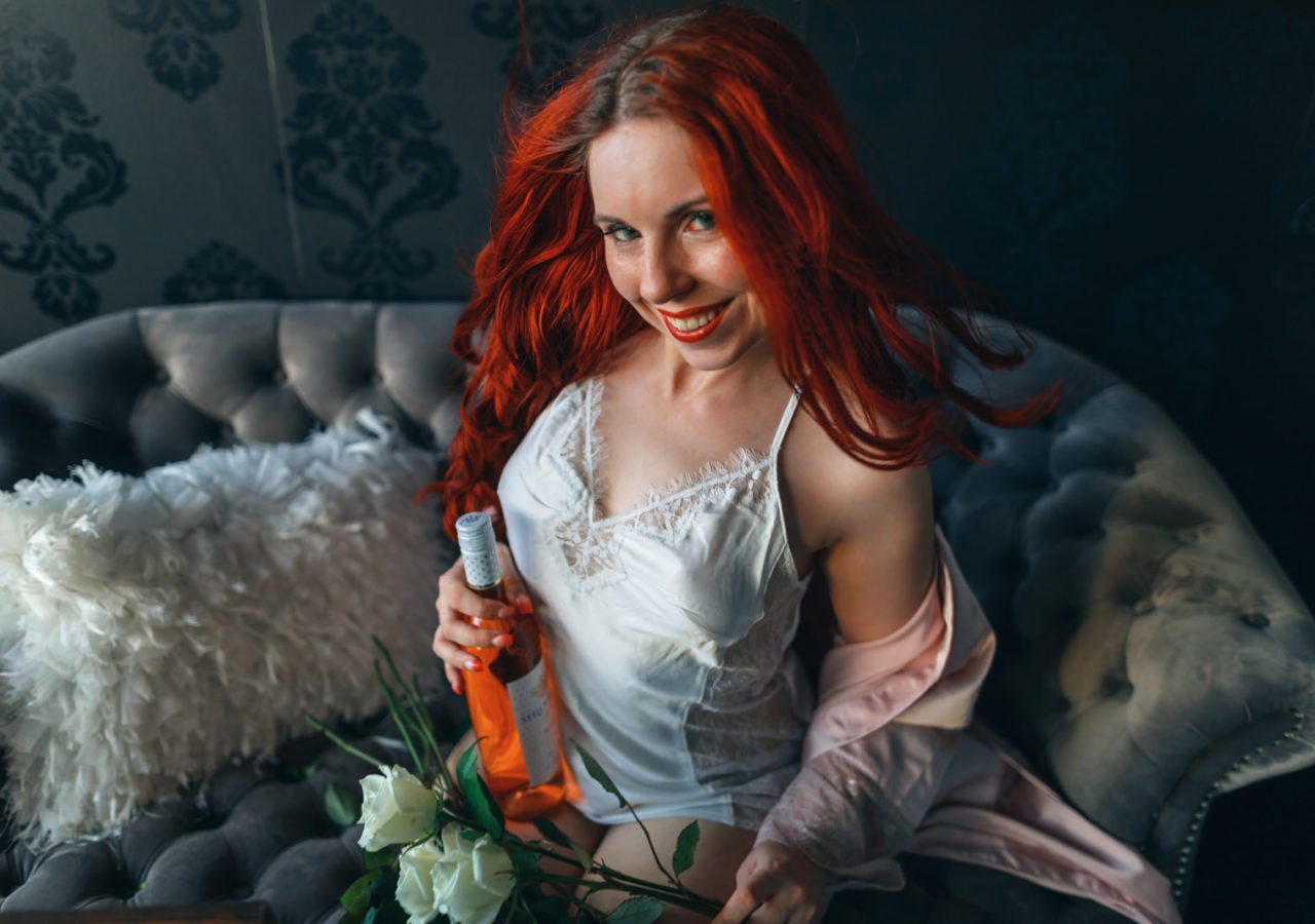 Young red hair bride holding bottle of wine for wedding boudoir photography photo shoot.