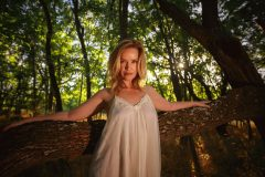 blonde woman in white silk nightie posing in forest with golden hour light at sunset behind her