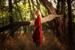 nude blonde woman with velvet red robe wrapped around her waist looking up at the sunset sky with the golden hour light shining bright behind her, through tree branches in a forest