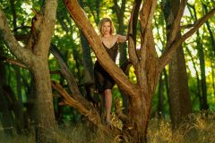 blond woman in black lingerie, with the golden sunlight shining behind her, posing like a black widow between tree branches