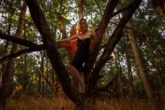 blond woman in black lingerie, with bright red light behind her, posing like a black widow between tree branches